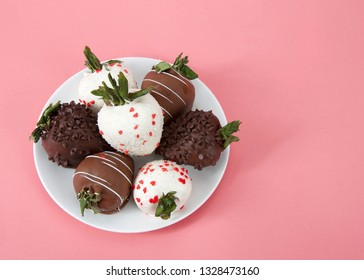 Variety of Chocolate covered strawberries on a plate. Dark, white and milk chocolate on a pink background. Top view.