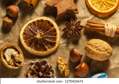 variety of christmas food products nuts cinnamon stick lollipop orange slice on gray paper