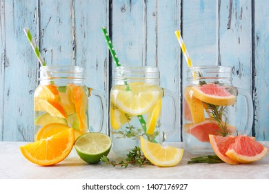 Variety of citrus infused detox water drinks in mason jar glasses against a blue wood background