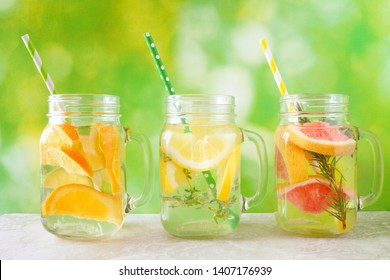 Variety of citrus infused detox water drinks in mason jar glasses against a summer background