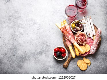 Variety of cold meat cuts and appetizers, red wine, prosciutto, jamon, salami slices, sausage, grissini, olives. Assorted mix of meat on rustic wooden board, space for text, top view, close-up