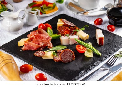 Variety of cold meats, bacon and sausages served on a slate board in restaurant table