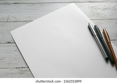 Variety color of ball pen on white paper background lay on white wooden background. Copy paste for text, logo and etc.