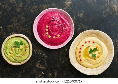 A variety of colored hummus, classic hummus, beet hummus, hummus with avocado on a dark rustic background. Top view, flat lay. Clean eating, dieting, vegetarian party food.