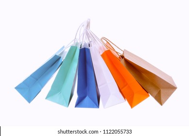 Variety of colored paper shopping bags on white background. Empty area.