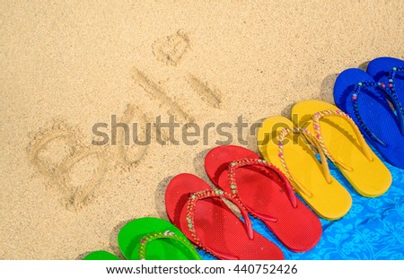 57bfff57e A variety of colored sandals at the beach with Bali written in the sand.