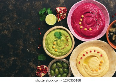 A variety of colored vegetarian hummus, caponata and olives on a dark background, copy space. Top view, flat lay