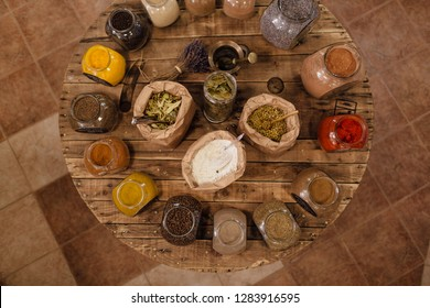 Variety of colorful dried herbs and spices displayed on wooden table in plastic free store. Top view of bags and glass jars full of whole and ground spices and herb leaves in packaging free shop.