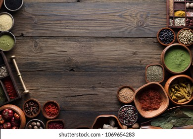 Variety of colorful dry spices  and herbs in teakwood bowls. Rustic wooden kitchen table. Indian and thai ingredients.
