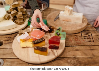 Variety of colorful homemade soap bars displayed on round wooden trays in zero waste store. Customer picking from various natural soap bars in packaging free shop.
