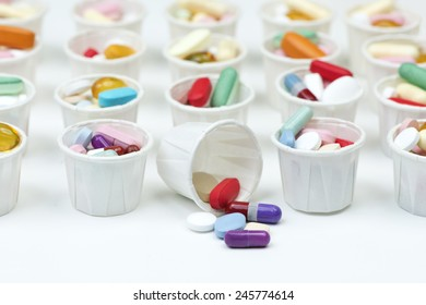 Variety of colorful pills arranged in white paper medication cups.