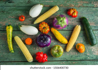 Variety of colorful red, green, yellow, white, tomatoes, zucchini, corn and eggplants over old green texture background. Healthy eating food background theme. Top view or flat lay.