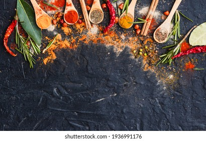 variety of colorful spices, herbs and hot chili peppers for cooking on dark background