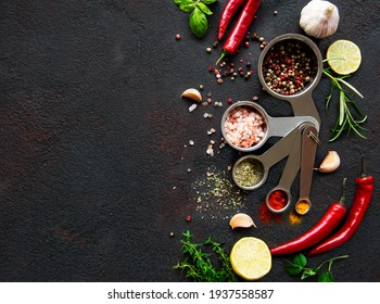 Variety of colorful spices in  spoons. Salt flakes, mixed pepper, rosemary, basil and garlic on dark black slate background. Top view. Copy space.