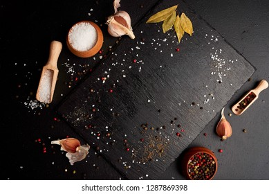 Variety of colorful spices in wooden spoons. Salt flakes, mixed pepper and dry chilli on dark black slate background. Top view