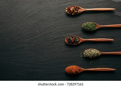 Variety of colorful spices in wooden spoons. Chilli flakes, mixed pepper, dry parsley, herbs and red paprika on dark black slate background. Top view. Copy space.