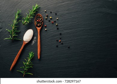 Variety of colorful spices in wooden spoons. Salt flakes, mixed pepper, and fresh rosemary on dark black slate background. Top view. Copy space.