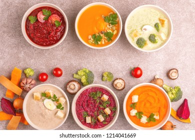 Variety of colorful tasty vegetables cream soups and fresh ingredients for soups. Healthy food concept or vegetarian food. Gray marble background