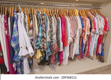 Variety of colorful womens clothing hanging on rail in fashion shop