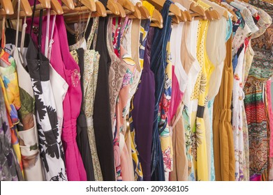 Variety of colorful womens summer clothing hanging on rail in fashion shop