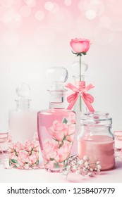 Variety of cosmetic product bottles with roses essence standing on white pink background with bokeh. Skin care, cosmetic shop, sale and abstract beauty concept