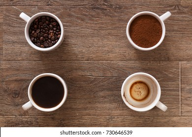Variety of cups of coffee and coffee beans on old wooden table. Four cups of coffee, phases of drink - bean, ground and empty cup.