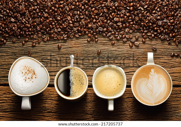 Variety of cups of coffee and coffee beans on old wooden table