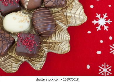 A variety of decadent chocolates arranged on a gold poinsettia plate, on a red felt snowflake mat.