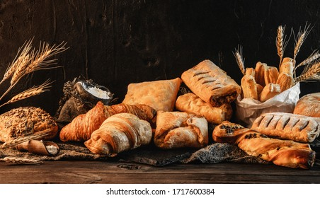 Variety of delicious breads and buns on dark rustic wooden background with wheat spikiletes. Pastries and bakery, space for text