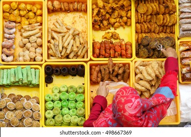 """Variety of delicious and colorful Malaysian home cooked local cakes or """"kueh"""" sold at street market stall in Kota Kinabalu Sabah from top angle view with seller arranging the cake."""