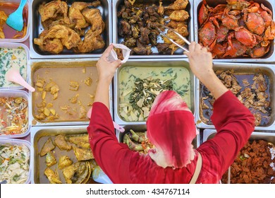 Variety of delicious Malaysian home cooked dishes sold at street market stall in Kota Kinabalu Sabah from top angle view with seller taking food.