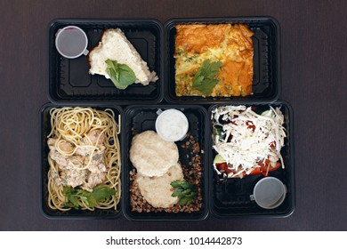A variety of dietary food in a plastic packaging on a wooden background, top view. The concept of healthy clean food