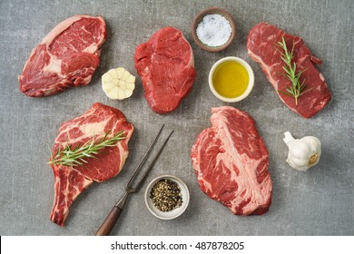 Variety of different beef steaks with ingredients on grey stone