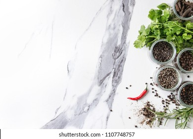 Variety of different black peppers allspice, pimento, long pepper, monks pepper, peppercorns in glass jars, chili pepper and fresh herbs in plate over white marble background. Top view, space.