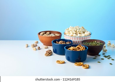 Variety different of cinema snacks in bowls pretzels, salted popcorn, pistachios, walnuts and pumpkin seeds. Blue backlight, copy space