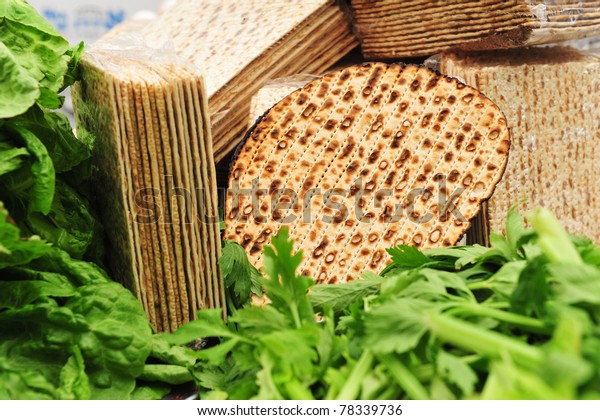 Variety of different types of matza (unleavened bread) surrounded by green vegetables such as lettuce and celery - traditional food used on the Jewish religious holiday feast of Passover ritual feast.