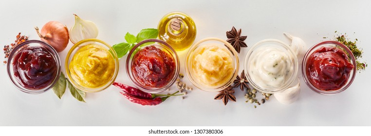 Variety of dips, marinades and sauces with spices, herbs and ingredients viewed top down in a row on white in a panorama banner