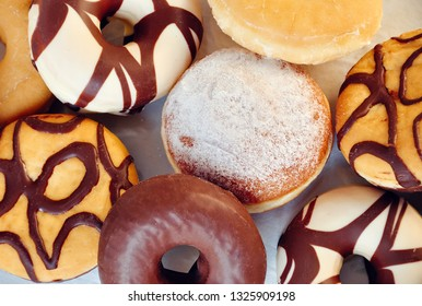 Variety of donuts with chocolate icing and powdered sugar. Donuts closeup top view .  Bakery and pastry background.