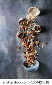 Variété de fruits secs, de noix, de miel et de flocons d'avoine tourbillonnent dans un bol en céramique pour cuisiner du muesli petit-déjeuner sain fait maison ou des barres d'énergie en granola sur fond texture bleu. Plat lay, espace.