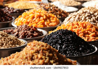 Variety of dried fruits on the market counter. Assorted dried fruits on display at farmers market.