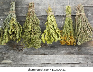 Variety of dried herbs and spices on an old wooden background