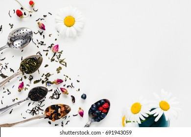 Variety of dried tea, dried herbal, green, black tea and fruit tea on vintage silverware tea spoons over white background with copy space / negative space. Table top view