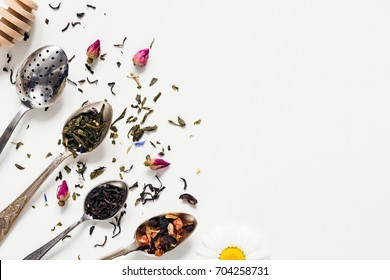 Variety of dried tea, dried herbal, green, black tea and fruit tea on vintage silverware tea spoons over white background with copy space negative space. Table top view