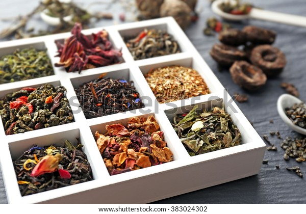 Variety of dry tea in wooden box with spoons on grey background