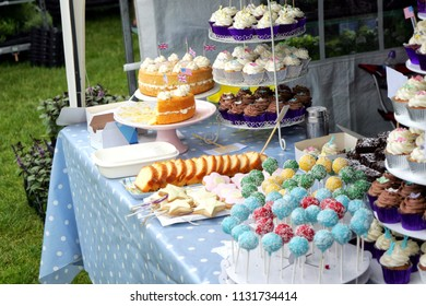 Variety of fancy cupcakes, lollipops and other cakes on display on a market stall