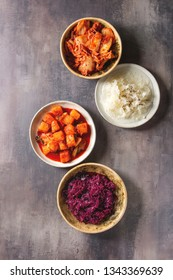 Variety of fermented food korean traditional kimchi cabbage and radish salad, white and red sauerkraut in ceramic plates over grey texture background. Flat lay, space