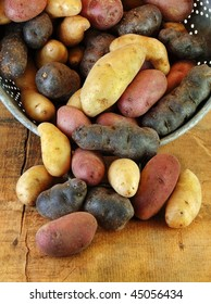 Variety of fingerling potatoes spilling out of a colander.