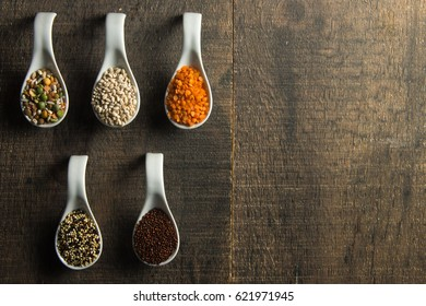 Variety of food and grains in spoons on rustic wood