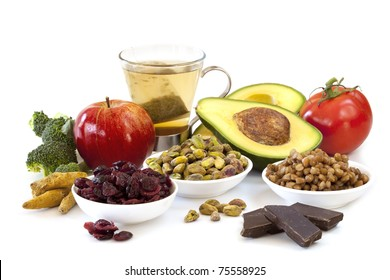 Variety of foods rich in antioxidants, isolated on white. Includes broccoli, apple, green tea, pistachios, cranberries, avocado, tomatoes, lentils and dark chocolate.