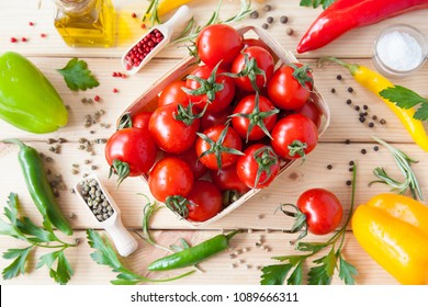 Variety of fresh appetizing vegetables and dry spices on wooden background, upper viewpoint